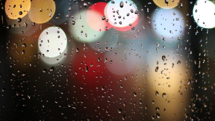 Krople deszczu na szybie z kolorowymi refleksami